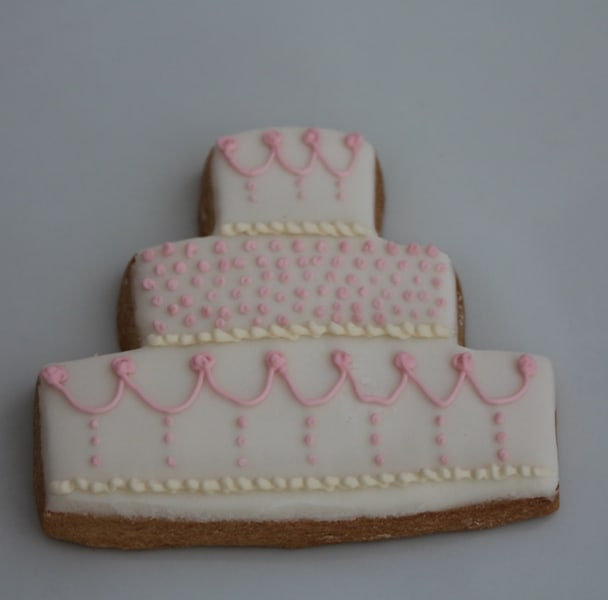 white wedding cake with pink detail cookie favour